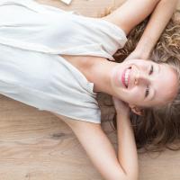 uśmiechnięta kobieta leży na drewnianej podłodze